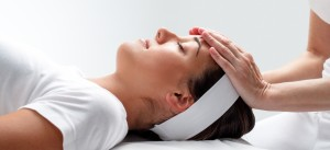 Close up portrait of young woman relaxing at reiki session.Therapist touching girls head with hands.